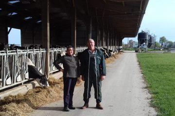 Couple d'agriculteurs, un homme et une femme, posant à l'extérieur près de la table d'alimentation de leur troupeau de vaches Prim'Holstein
