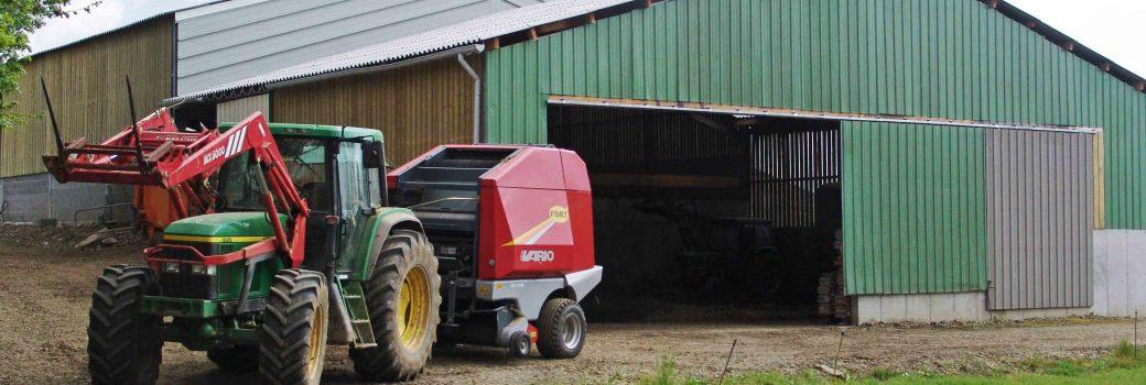 Abords d'une ferme de vache laitière avec devant un tracteur vert équipé d'une presse